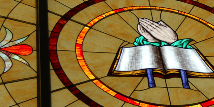 Stained Glass Window with Open Book and Hands in Prayer