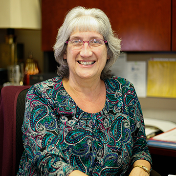 Older Woman with Gray Hair Sitting at Desk and Smiling for Photo