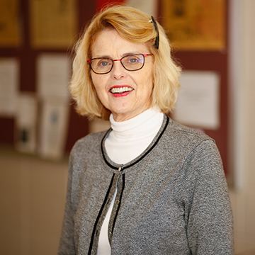 Woman with Blond Hair and Glasses with Gray Cardigan Posing for Photo