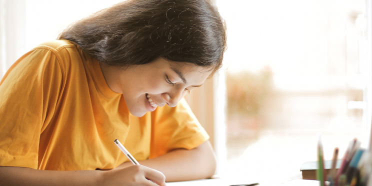 A student writes at a desk.