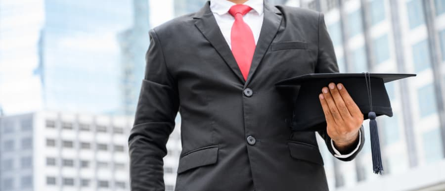 Business professional holding graduation cap