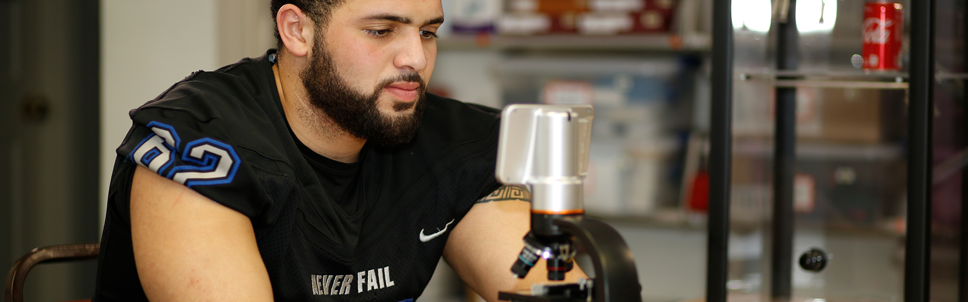 Student athlete in criminal justice major studying with microscope