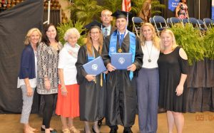 Tammy Wilson and Hunter Wilson, center, stood with family and friends following thier graduation from Faulkner University.
