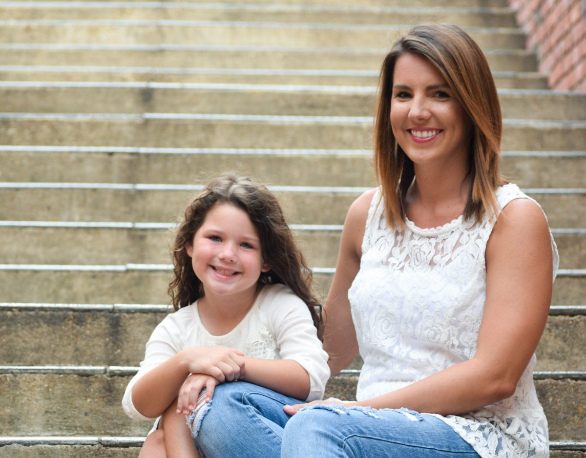 Meghan Harris and daughter, Ollie sit on concrete steps.