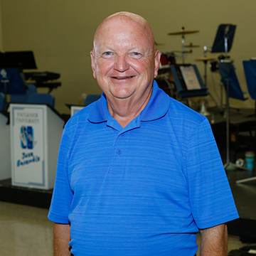 Older Man with Blue Shirt Posing for Photo in Band Room
