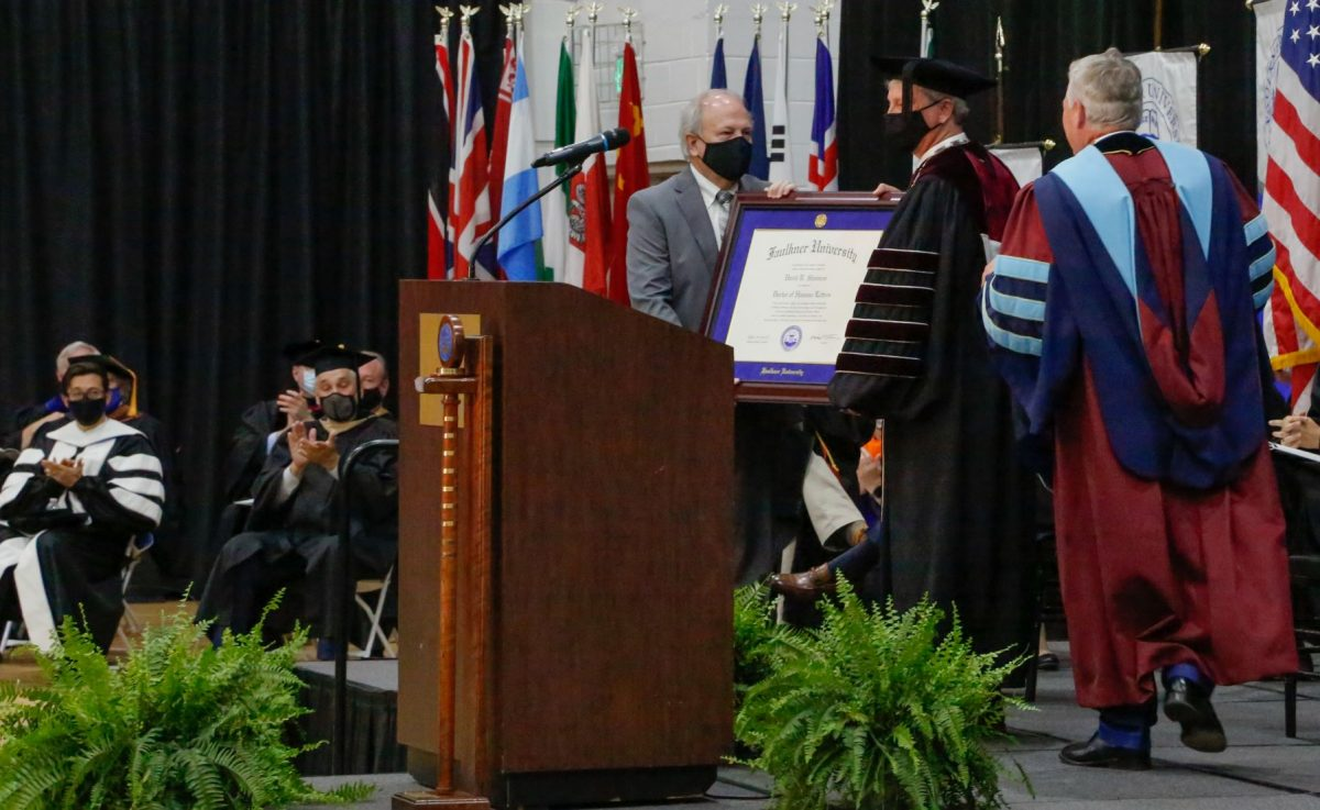 Dale Kirkland, left and President Mike Williams, right confer an honorary Doctorate of Humane Letters to David Shannon, center.