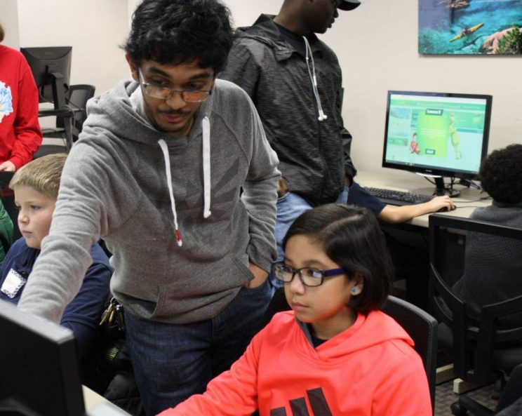 Javan Rampersad helps a fifth-grade student code as a volunteer mentor for a Day of Coding, an annual event at Faulkner, which allows Computer Science majors to introduce basic coding skills to students from area schools.