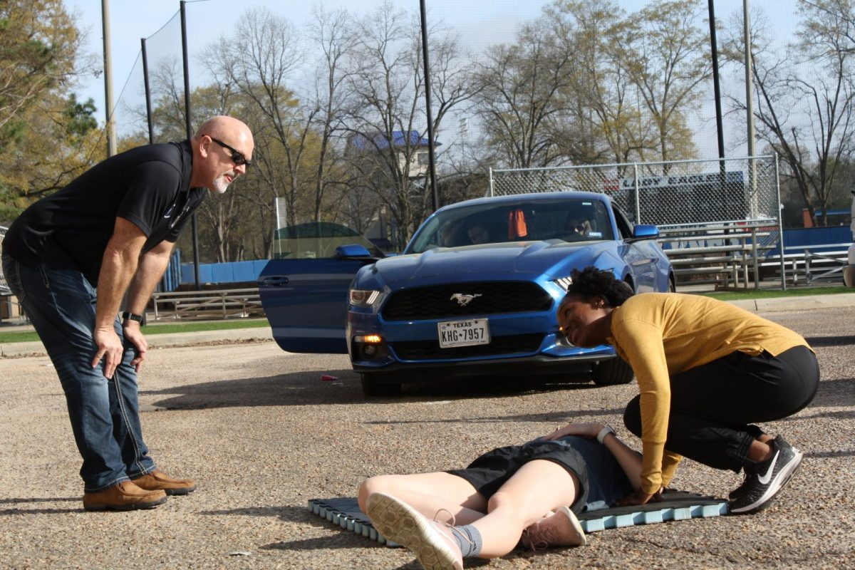 """Student assesses the responsiveness of her """"unconscious"""" peer during a First-Aid CPR class demonstration."""