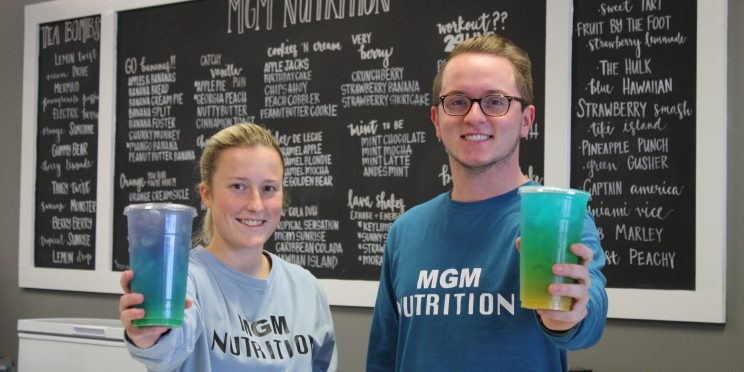 Brianna Cagle, left and Logan Wallace hold up drinks in their store, MGM Nutrition.