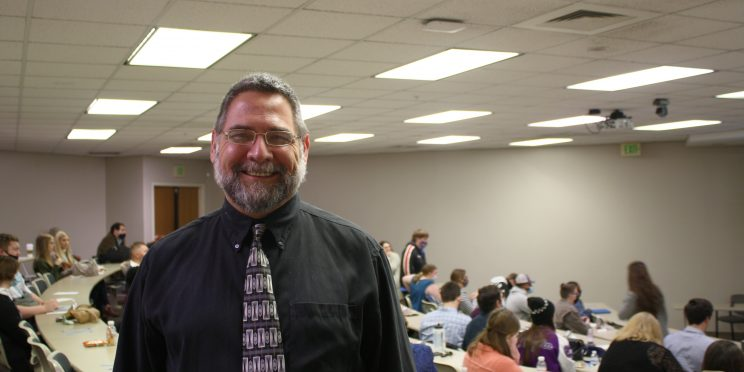 """Franklin """"Buddy"""" Renahan is an adoption family counselor. He stands in an auditorium full of students ready to speak during the Marketplace Faith Friday Forums 2021."""