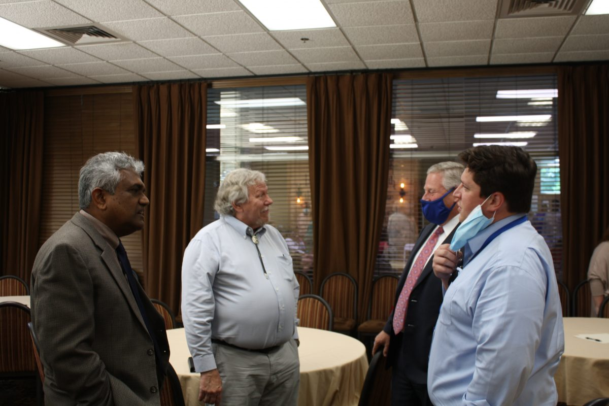l-r Dr. Dave Rampersad, Dr. Al Schlundt, President Mike Williams and Wesley Schlundt chat during Al Schlundt's retirement ceremony. Schlundt served as a biologist and an educator.