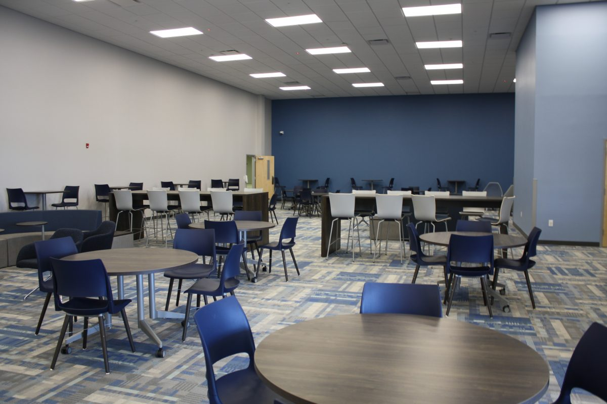 Renovations of the College of Health Sciences include blue painted walls, blue and gray patterned carpeting and tables and chairs in the lobby area.