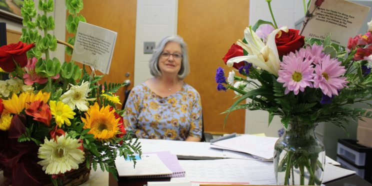 Barbara Kelly sits at her desk surrounded by two large bouquet of flowers.