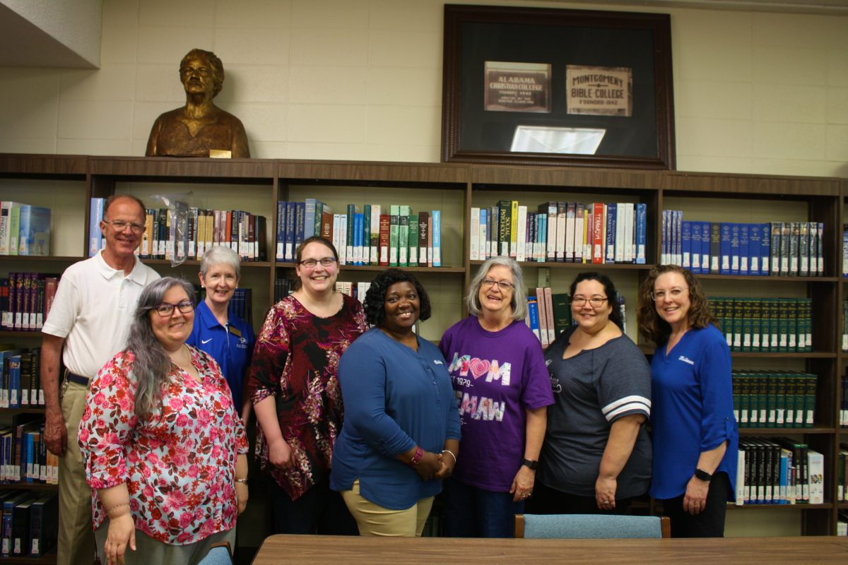 Barbara Kelly stands among her colleagues at the Gus Nichols Library.