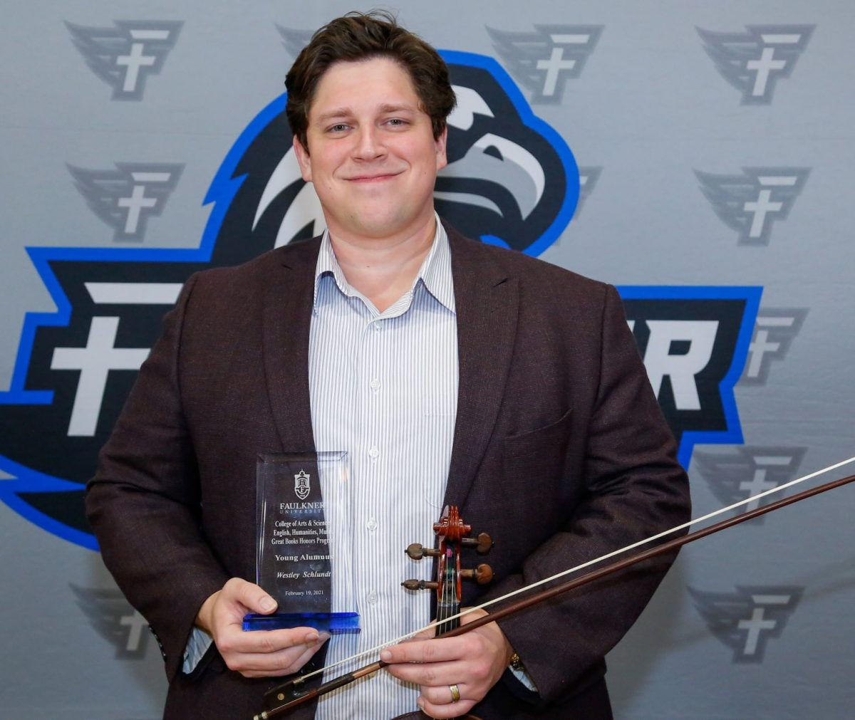 Westley Schlundt holds his violin and award. As a musician, he was honored as the Faulkner Young Alumnus for the Music Department.