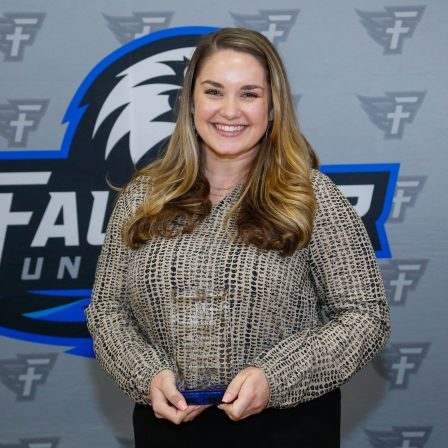 Hannah Putman stands with her award at the Marketplace Faith Friday Forums.As a microbiologist with the Alabama Department of Public Health, (ADPH) Faulkner alumna Hannah Putman is working to combat illnesses and make a positive difference in people's lives.