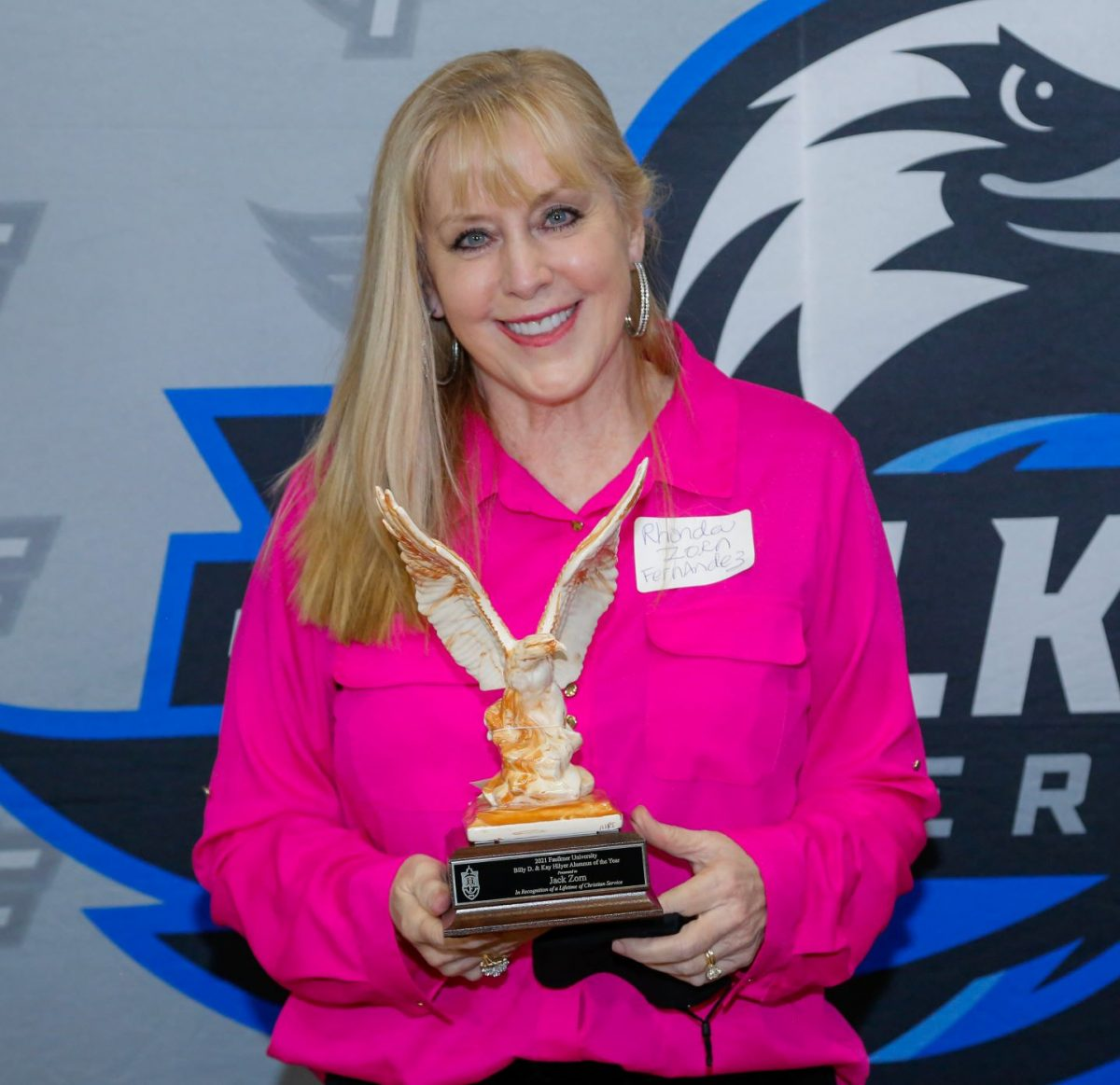 Rhonda Fernandez holds her father's Alumnus of the Year Award, an Alabama Clay eagle with its wings in flight.