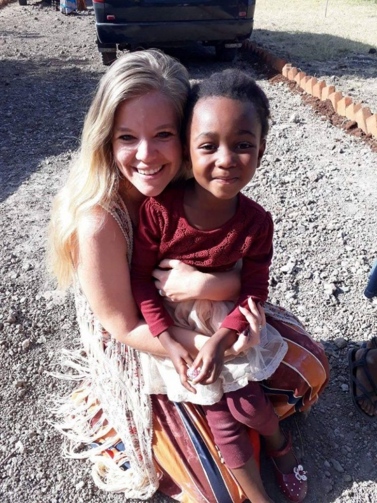 Anna Maynard holds a child from the village they serve in Tanzania, Africa.