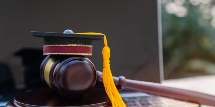 Laptop Beside Judge's Gavel And Graduation Cap