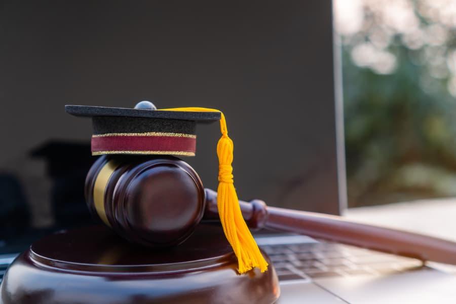 Laptop Beside Judge's Gavel And Graduation Cap