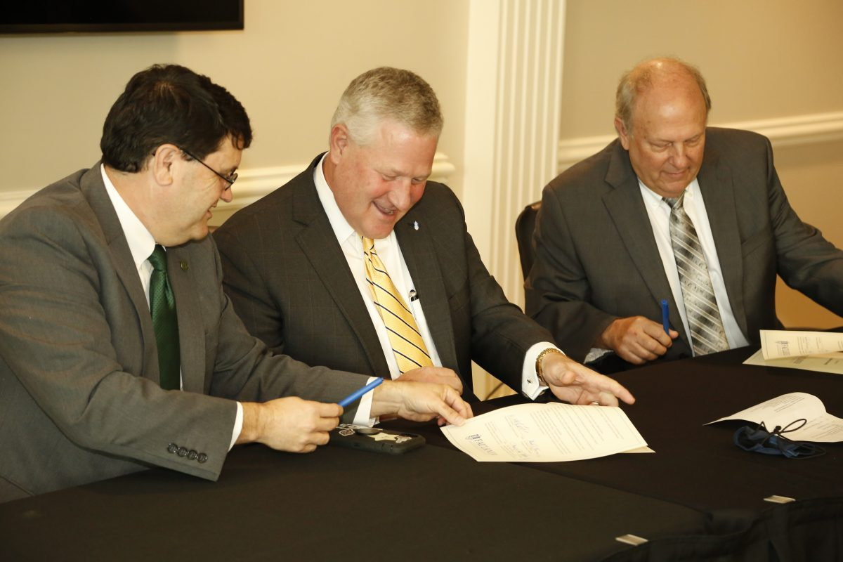 l-r W. Kirk Brothers, Mike Williams and Dale Kirkland sign a Memorandum of Understanding with Heritage Christian on Faulkner's Montgomery campus on September 30, 2021.