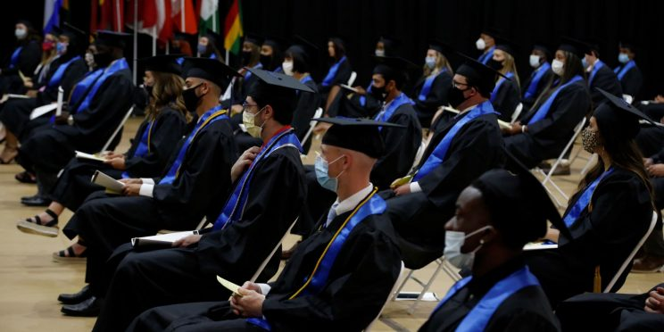 Graduates spaced 6-feet apart wait to walk the stage during 2020 Spring commencement ceremony.