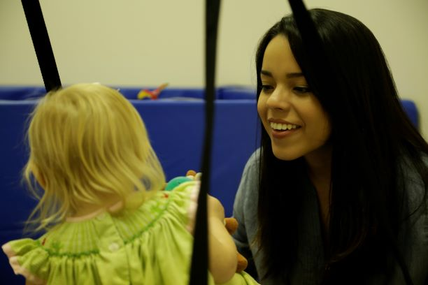 Faulkner student, Esther Barahona works with a young patient inside the clinic's fun physical therapy room.