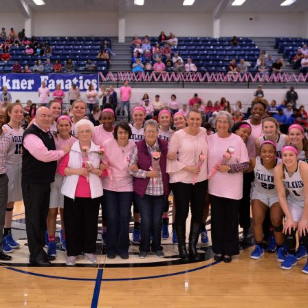 Breast Cancer survivors pose with the Faulkner Women's Basketball team during their PinkOut game in 2019.