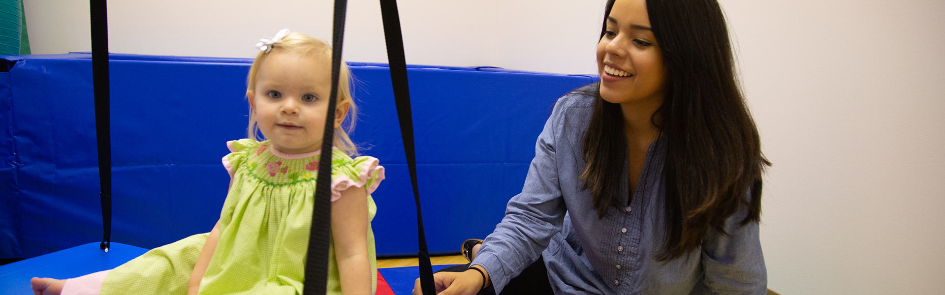 A Faulkner Speech Language Pathology student aiding an infant