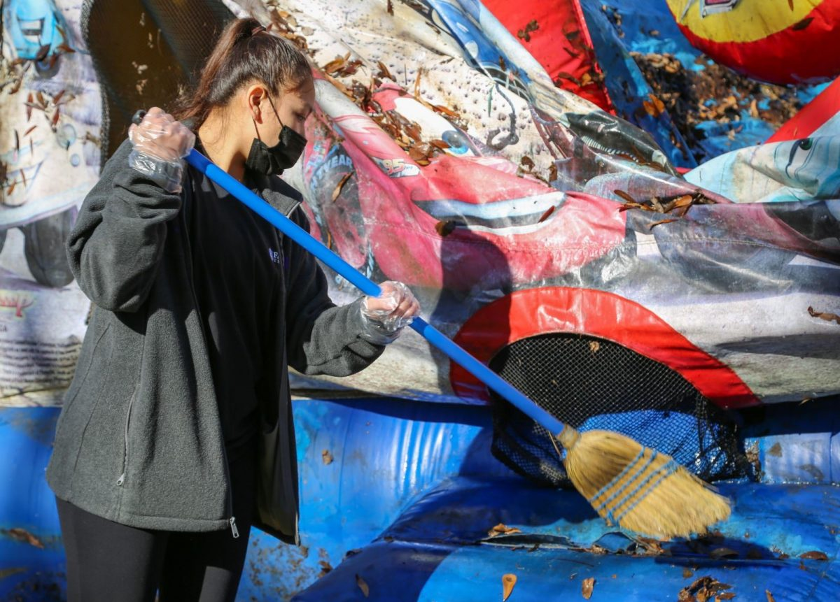 A Faulkner student brushes leaves and debris off an outside inflatable play house at Mercy House on MLK Day, January 18, 2021.