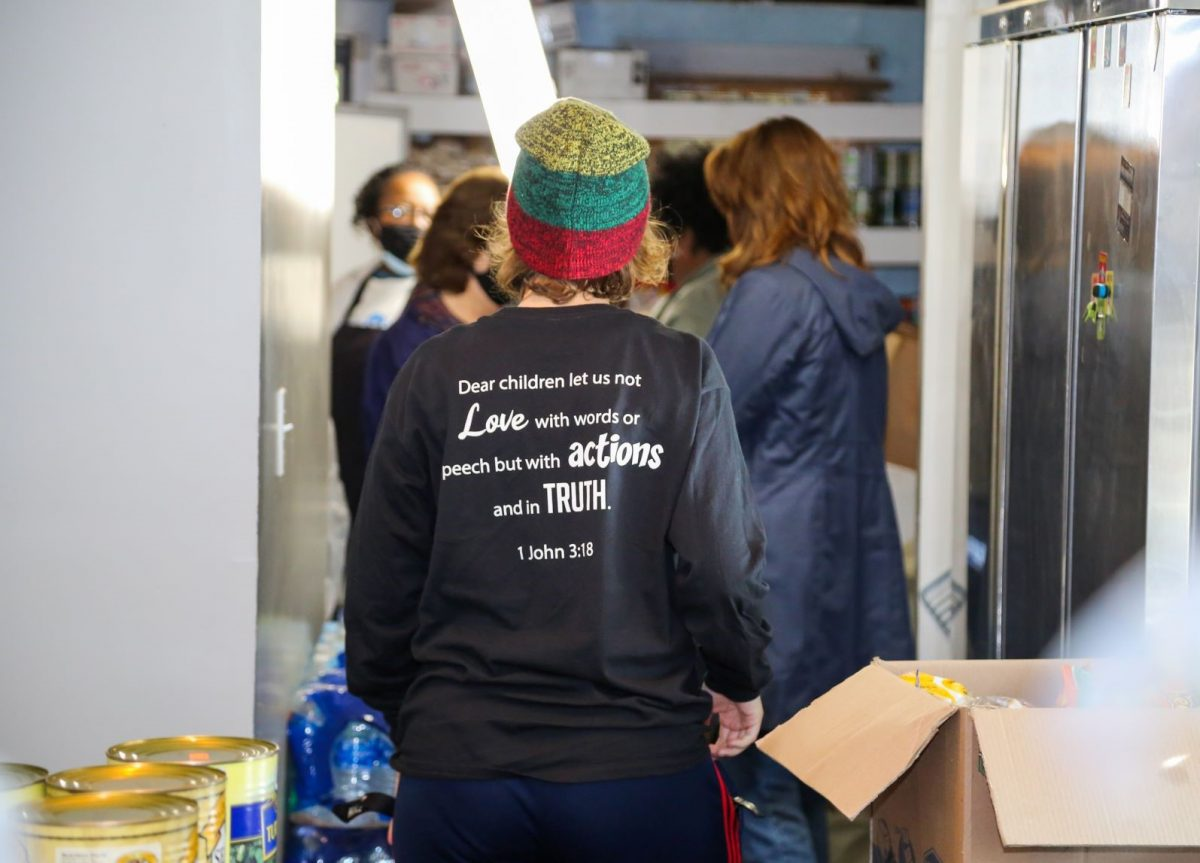 "A student volunteer helps in the Mercy House kitchen. On the back of her Faulkner volunteer shirt is written the verse from 1 John 3:18, ""Dear children let us not love with words or speech but with actions and in truth."""