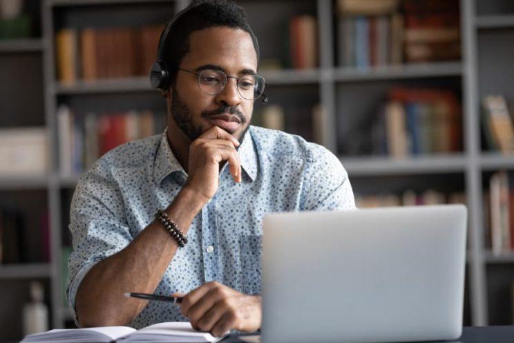 Student wearing headphones studying on laptop