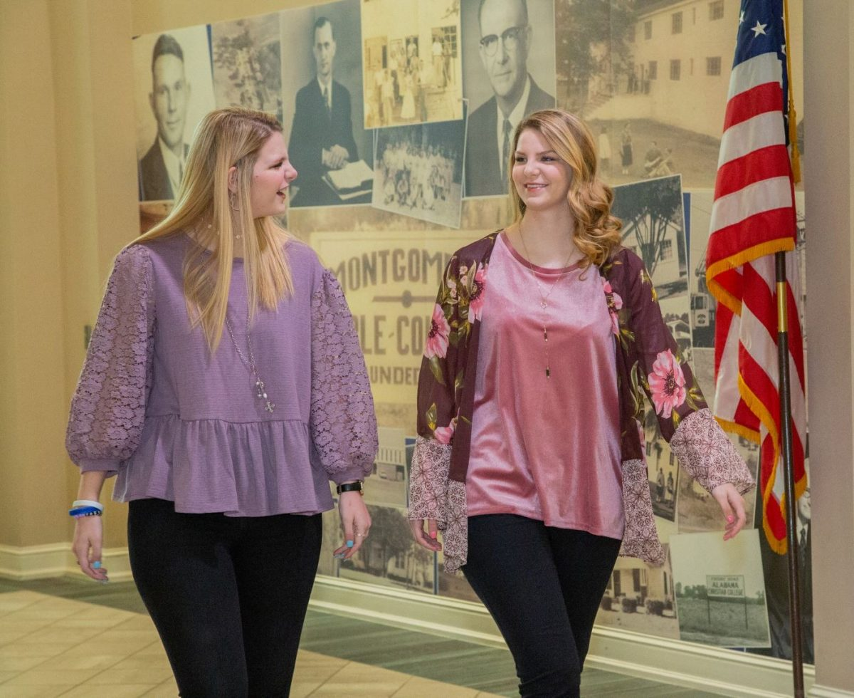 l-r: Victoria McDaniel and her sister Olivia McDaniel chat as the walk a corridor of campus.