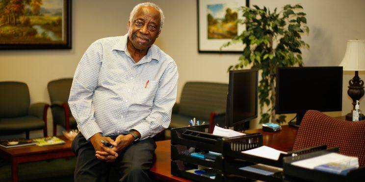 Michael Walcott Sitting on Desk