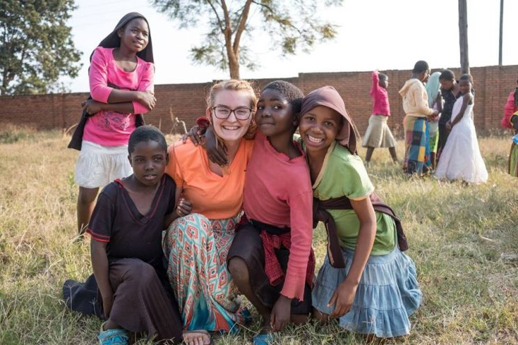 Ashley Ingwersen poses with children she served in the Mtendere Village in Malawi.