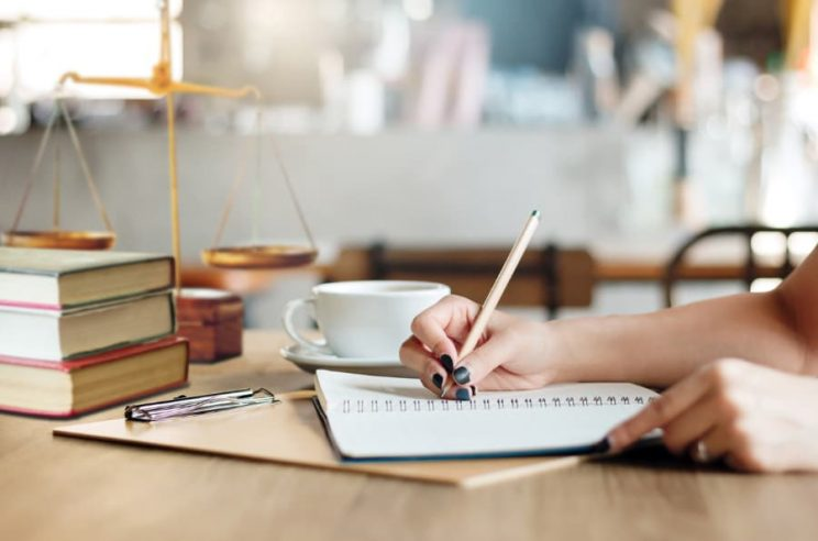 Woman writes on paper with scales of justice in background