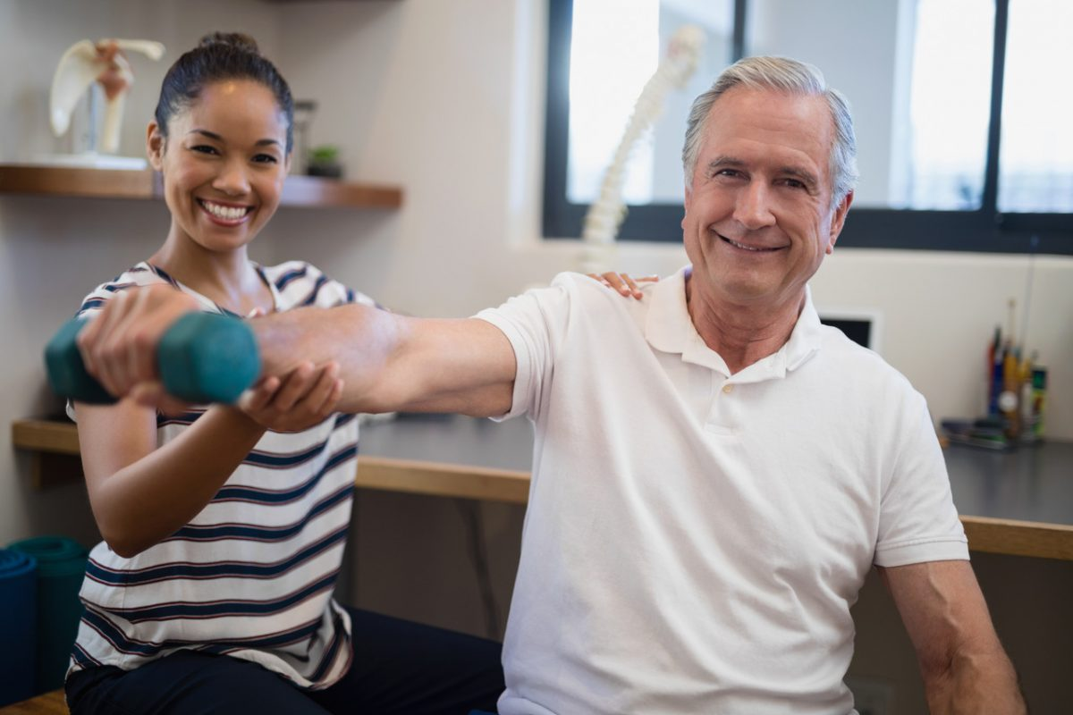 Therapist helps elderly patient with physical therapy exercises using a dumbbell. Physical Therapy is the most recent addition to Faulkner's programs after receiving accreditation status.