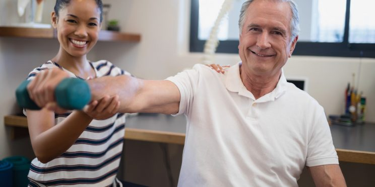 Therapist helps elderly patient with physical therapy exercises using a dumbbell