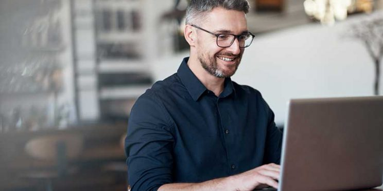 Man With Glasses Typing at Laptop