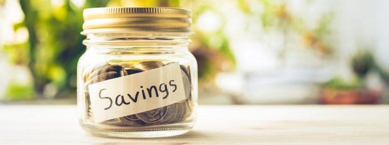 Savings money in glass jar.