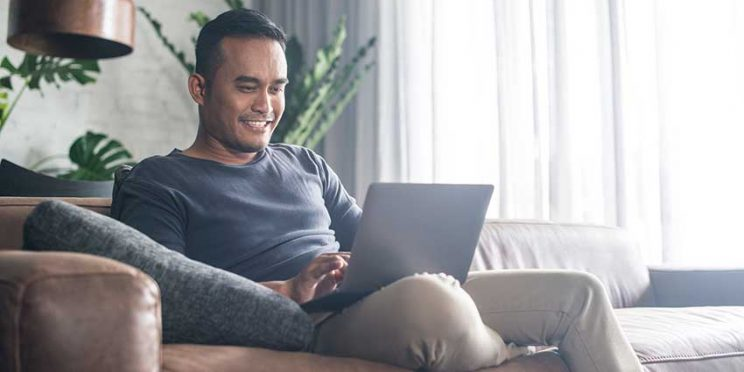 Man on Couch Typing on Laptop