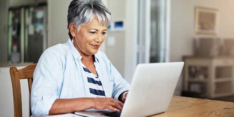 Older Woman Sitting at Table Typing on Laptop