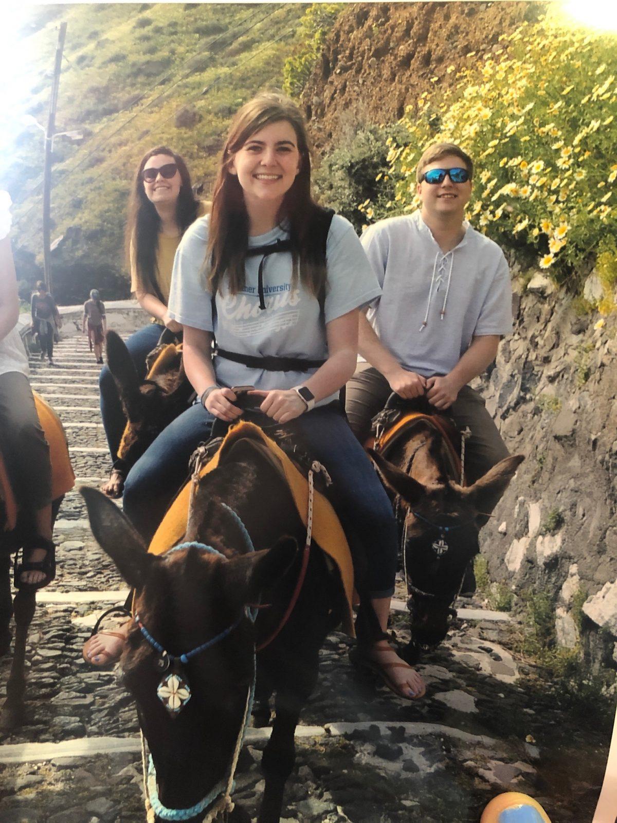 Students ride donkeys in Santorini, Greece.